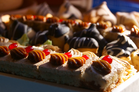 Many little pieces of cake and various tarts in a box