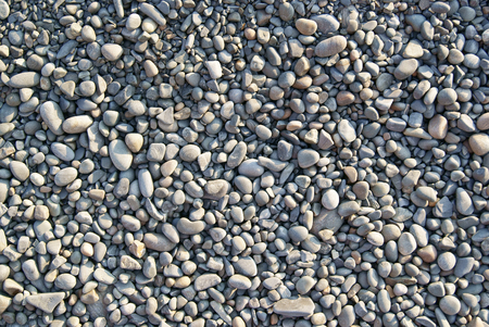 Background of light gray gravel waterworn pebbles on sea beach