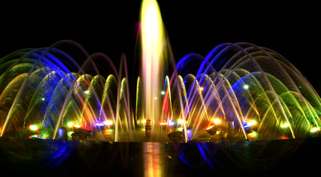 Close detailed view of dancing fountain at night, mix colored lighting decoration