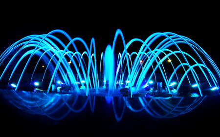 Close detailed view of dancing fountain at night, blue lighting decoration Stock Photo