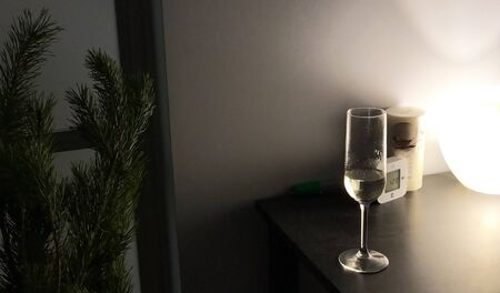 Glass of champagne on black table on Christmas Eve