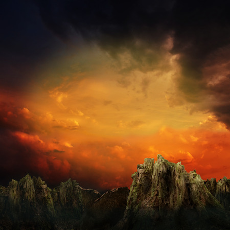 Dramatic sunset over mountains and rocks in fantasy land 写真素材