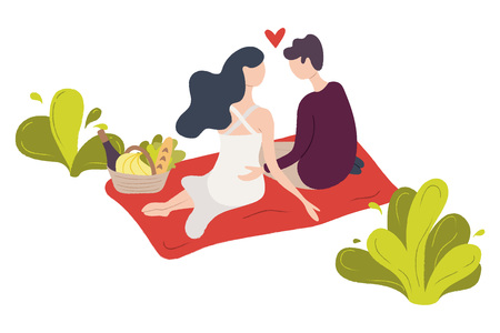 A couple of young people sitting on a blanket in a park. A pair of man and woman in love.
