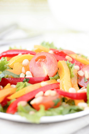 Salad with bell peppers, cherry tomatoes, cashew nuts and greens.