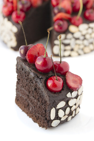 Chocolate cake with cherries on a white background. Stock Photo