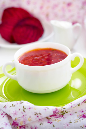 Red Ukrainian borsch soup with sour cream in a white plate.