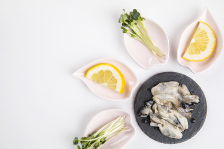 fresh oysters in a black plate on white background.