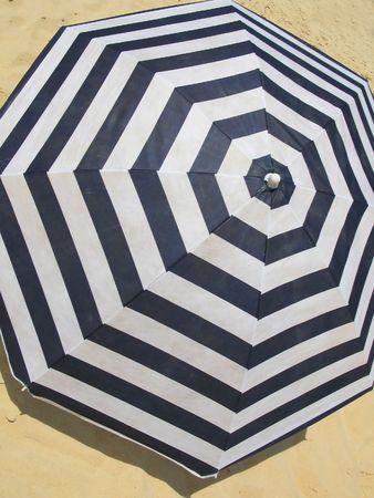 brolly: Striped umbrella on a sandy beach   Stock Photo