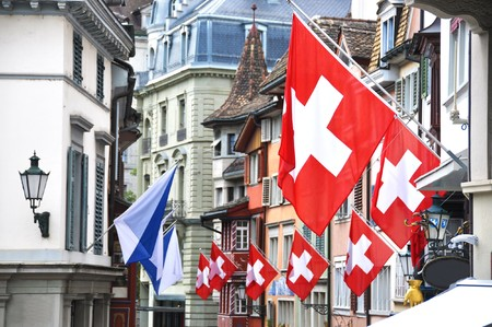 helvetica: Old street in Zurich decorated with flags for the Swiss National Day, 1st of August