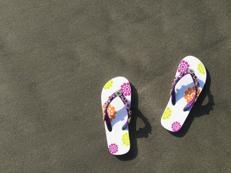Flip-flops and hat on the black sand of Tenerife island, Canaries photo