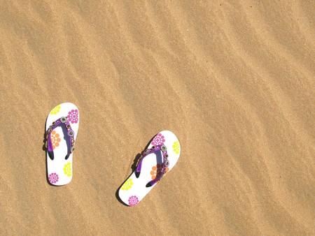 Trendy flip-flops on the sand photo