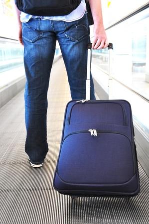 Reisende mit einem Koffer auf dem speedwalk