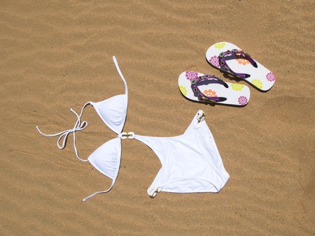 Bikini and flip-flops on the sand photo