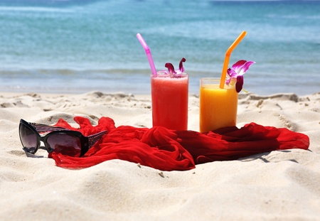 Pair of fruit shakes, red shawl and sunglasses on the tropical beach  photo