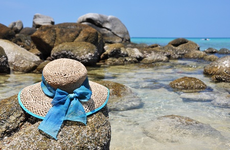 Straw hat on the rock. Phuket island, Thailand  photo