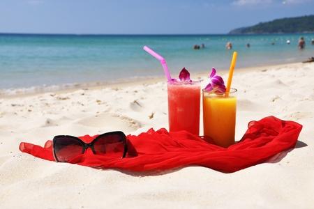 Pair of fruit shakes, red shawl and sunglasses on the beach of Phuket island Standard-Bild