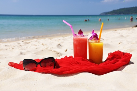 Pair of fruit shakes, red shawl and sunglasses on the beach of Phuket island Stock Photo
