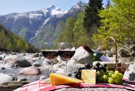 Rotwein, Käse und Trauben serviert bei einem Picknick. Verzasca-Tal, Schweiz