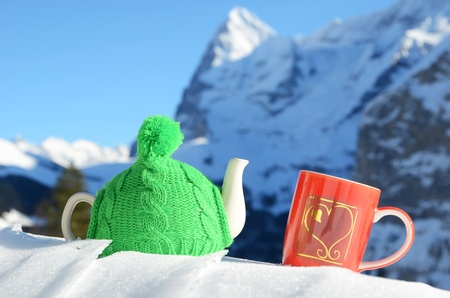 Tea pot in the knitted cap and red cup with a heart in the snow Stock Photo - 12248812