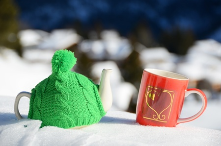 Tea pot in the knitted cap and red cup with a heart in the snow Stock Photo - 12248817