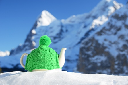 Tea pot in the knitted cap on the snow against mountain peak photo