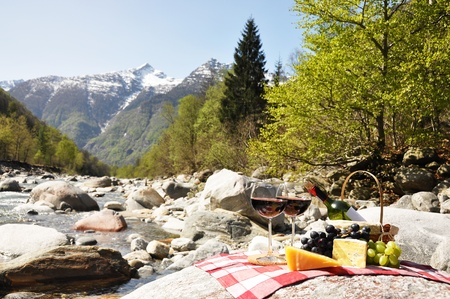 Red wine, cheese and grapes served at a picnic. Verzasca valley, Switzerland  photo