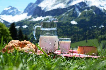 Milk, cheese and bread against Alpine scenery photo