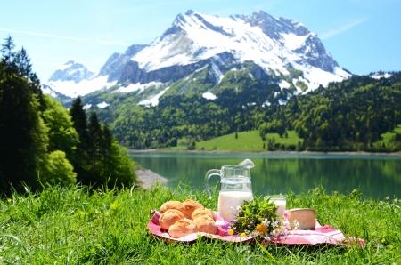 Milch, Käse und Brot bei einem Picknick auf Almwiese serviert, Schweiz