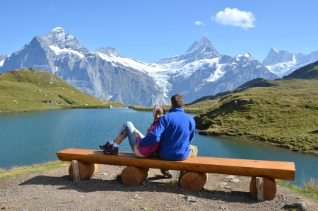 Travelers on a bench enjoying Alpine panorama  Jungfrau region, Switzerland  photo