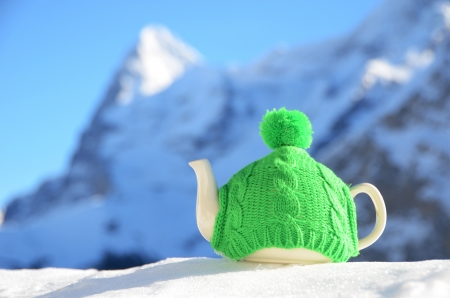 Tea pot in the knitted cap on the snow Stock Photo - 16006761