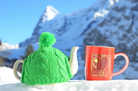 Tea pot in the cap and a cup against alpine scenery photo