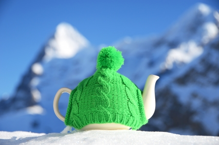 Tea pot in the knitted cap on the snow against mountain peak Stock Photo - 16256432