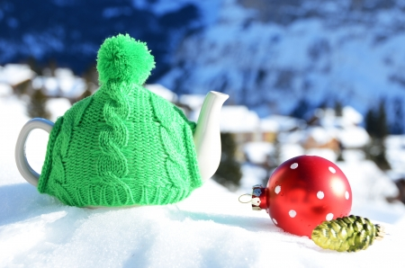 Tea pot in the cap against alpine scenery  photo