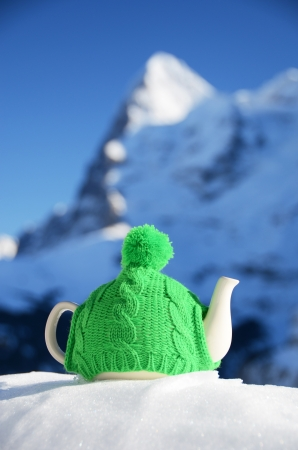 Tea pot in the knitted cap on the snow Stock Photo - 16829663