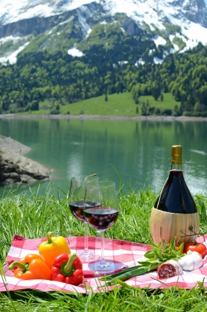 dinner date: Wine and vegetables served at picnic on Alpine meadow. Switzerland