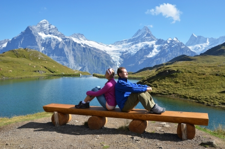 Travelers on a bench enjoying Alpine panorama. Jungfrau region, Switzerland  Stock Photo - 18438302