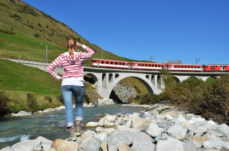 Girl looking at the train, which crosses a bridge. Switzerland photo