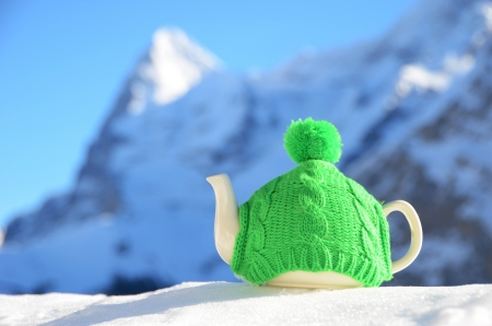 Tea pot in the knitted cap on the snow Stock Photo - 16877178