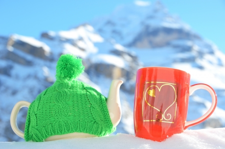 Tea pot in the cap and a cup against alpine scenery  Stock Photo - 16942671