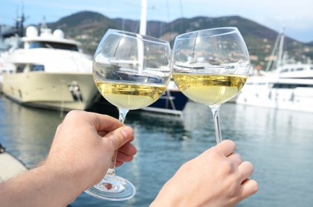 spezia: Pair of wineglasses in the hands against the yacht pier of La Spezia, Italy  Stock Photo