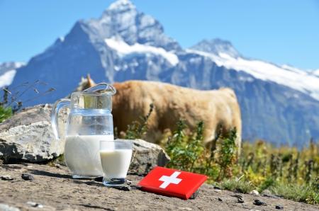 Swiss chocolate and jug of milk against mountain peak  Switzerland photo