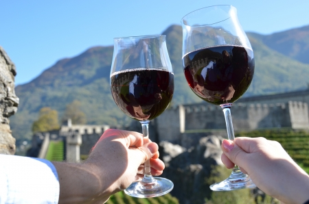 Pair of wineglasses in the hands  Bellinzona, Switzerland photo