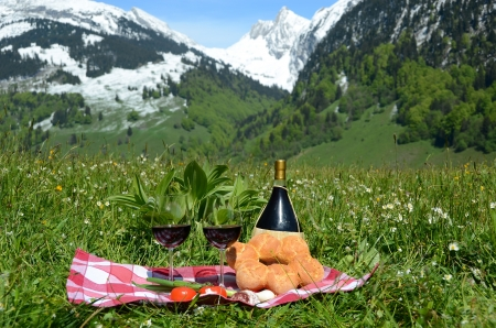 Wine and vegetables served at picnic on Alpine meadow  Switzerland  photo