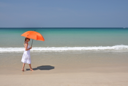 Girl with an orange umbrella on the sandy beach photo
