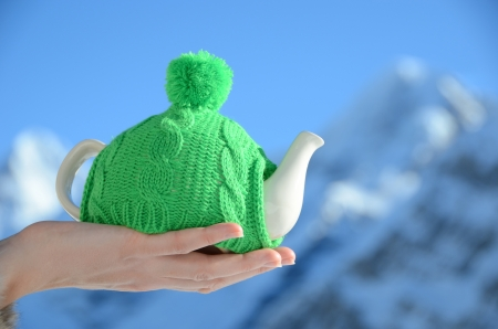 Tea pot in the knotted cap in the hand against alpine scenery  photo