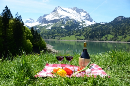 Wine and vegetables served at a picnic in Alpine meadow  Switzerland