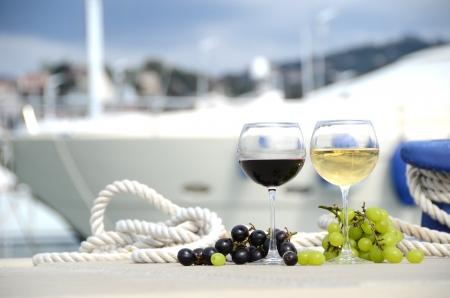 yachts: Coppia di bicchieri da vino e uva contro il molo turistico di La Spezia, Italia Archivio Fotografico