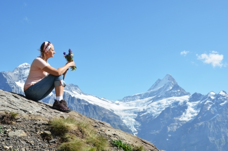 altitude: Girl sitting on a rock against Swiss Alps  Stock Photo