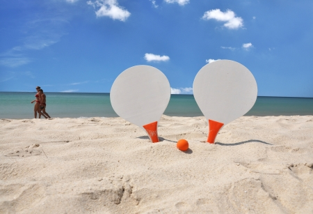 rackets: Two rackets and a ball on the sandy beach