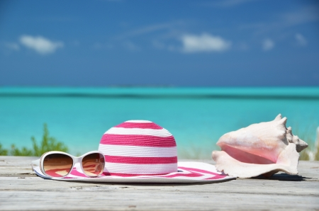 pink hat: Sunglasses, hat and shell against ocean. Exuma, Bahamas